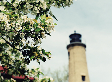 A lighthouse appears through the trees during a beautiful spring day in Kenosha.